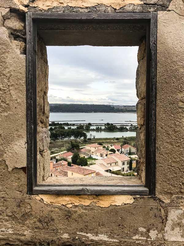Durch eine Maueröffnung an der Église Saint Saveur eröffnet sich der Blick auf den Étang de l'Estomac