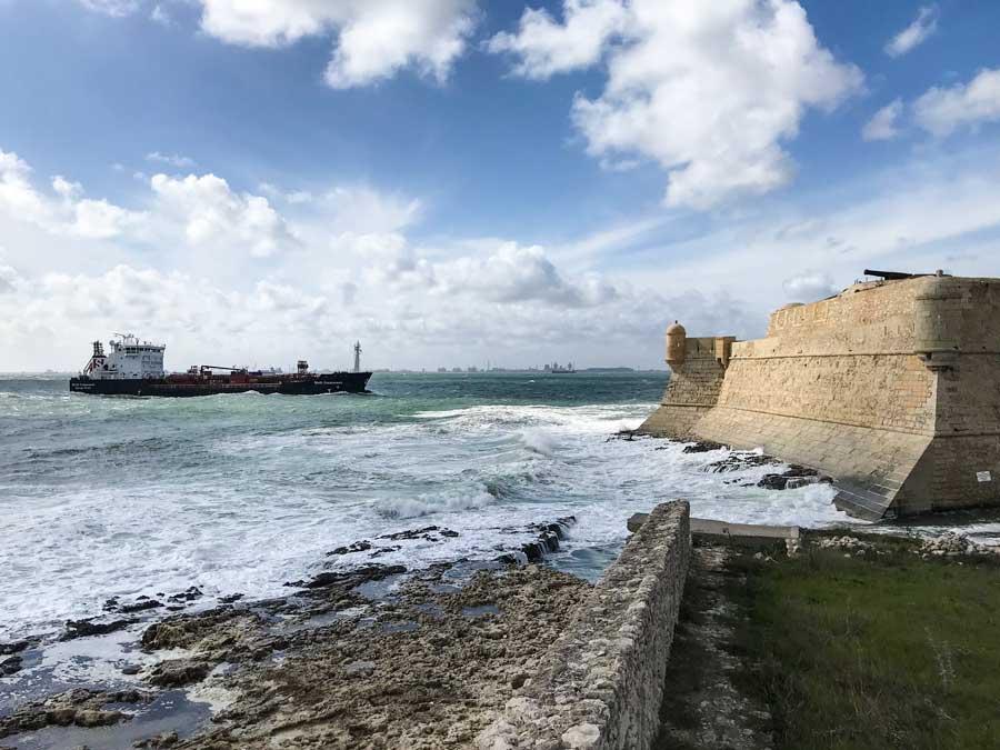 Ein Frachtschiff fährt in den Hafen von Port-de-Bouc ein und passiert dabei die Festung