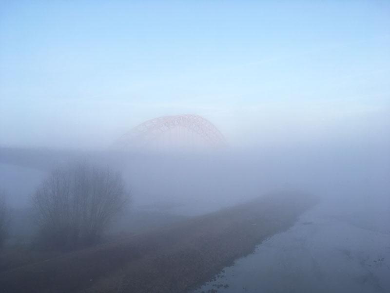 Die Brücke über die Waal schimmert in der Morgensonne über den Nebelbänken