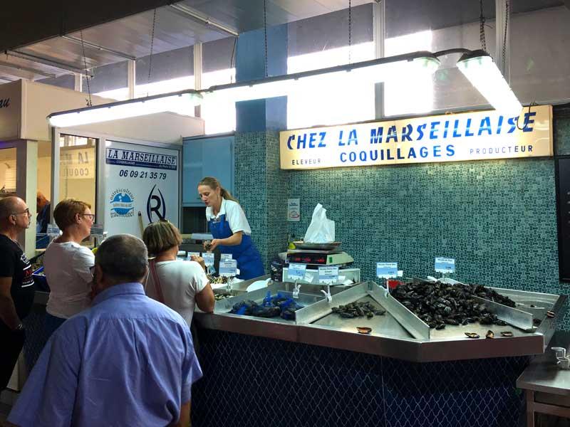 Es gibt viele Stände in der Markthalle, die lokale Meeresfrüchte verkaufen