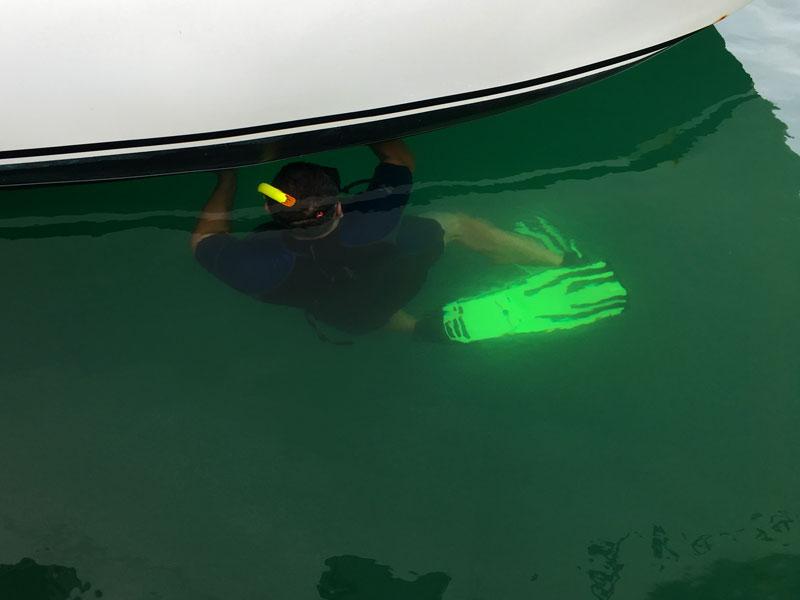 Thomas taucht mit dem Schnorcheln nach dem Bug-Seitenstrahler und beseitigt den Bewuchs des Propellers