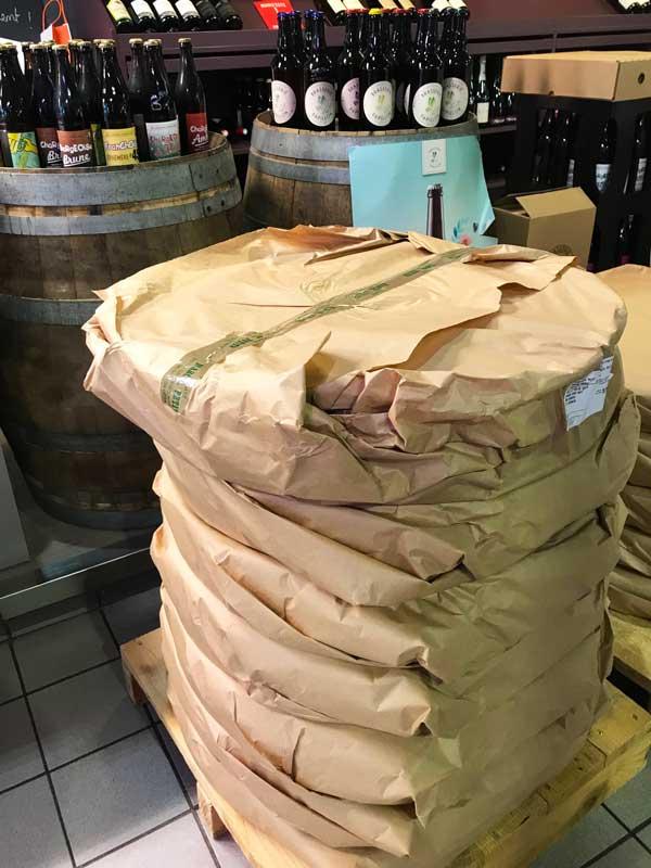 Käse- und Weinstand im Marché Couvert mit einem riesigen Stapel Comté