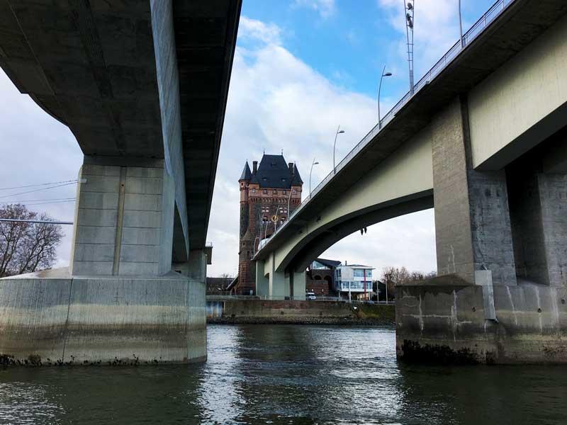 Zwischen zwei massiven Betonbrücken kann man bei Worms einen wunderschönen alten Turm sehen