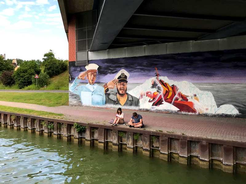 Schönes Graffiti mit Seemännern unter einer Brücke über den Dortmund-Ems-Kanal