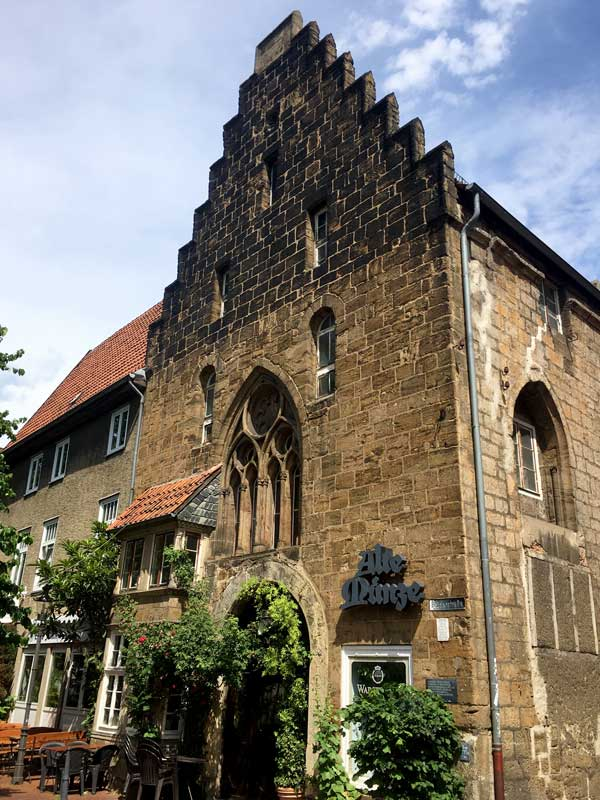 Die altes Münze in Minden ist ein Bau aus großen Steinquadern. Das Haus hat einen gestuften Giebel und Fenster, die an gotische Kirchenfenster erinnern