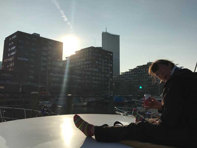 Wir trinken ein Bier auf dem Vordeck, während die Sonne hinter der an die City Marina Rotterdam angrenzenden Wohnbebauung untergeht