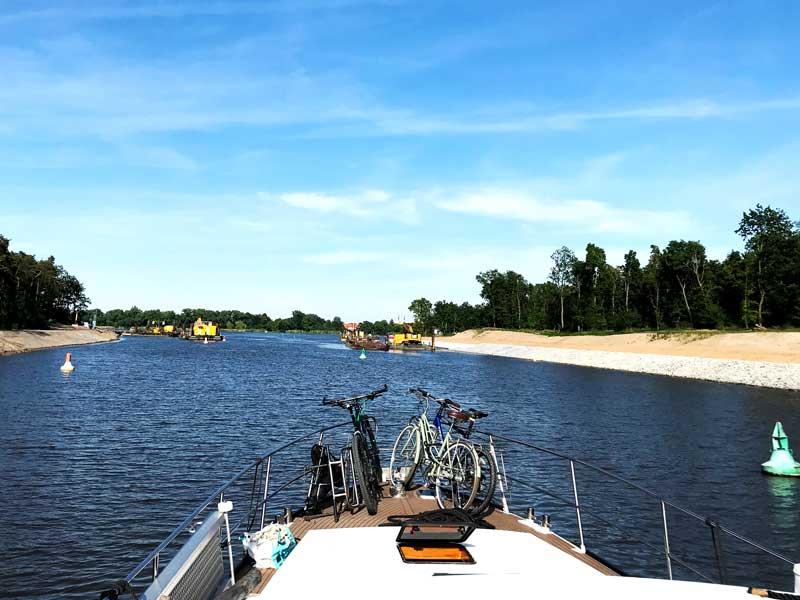 Die Fahrrine ist an dieser Stelle im Elbe-Havel-Kanal hinter der Schleuse Wusterwitz durch eine Baustelle stark verengt. Rote und grüne Tonnen begrenzen die Fahrrinne, rechts und links liege große Arbeitsplattformen im Kanal