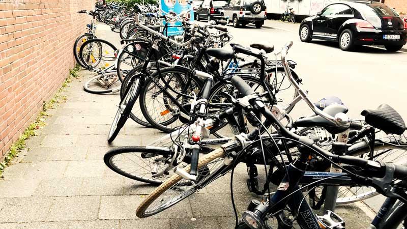 Fahrräder kreuz und quer auf dem ganzen Gehsteig