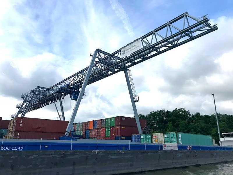 Ein Frachtschiff liegt im Hafen Braunschweig am Quai und wird von einem riesigen Kran mit Schiffscontainern beladen