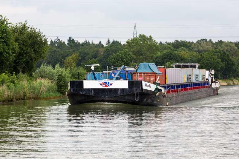 Auf dem Mittellandkanal zwischen Minden und Hannover: Das Steuerhaus des Containerschiffs Charly ist soweit hochgefahren, dass der Kapitän über die Container drübergucken kann