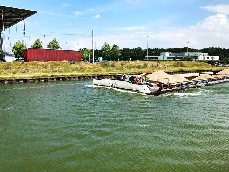 Direkt vor uns passiert ein Frachtschiff die schmale Hafeneinfahrt. Links ist noch das Dach der Volkswagenarena zu sehen, rechts hinten die Geschäftsstelle des VfL Wolfsburg