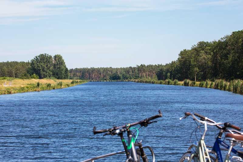 Der Elbe-Havel-Kanal erstreckt sich vor dem Bug in tiefem Blau, zu beiden Seiten Wiesen und Kiefernwälder
