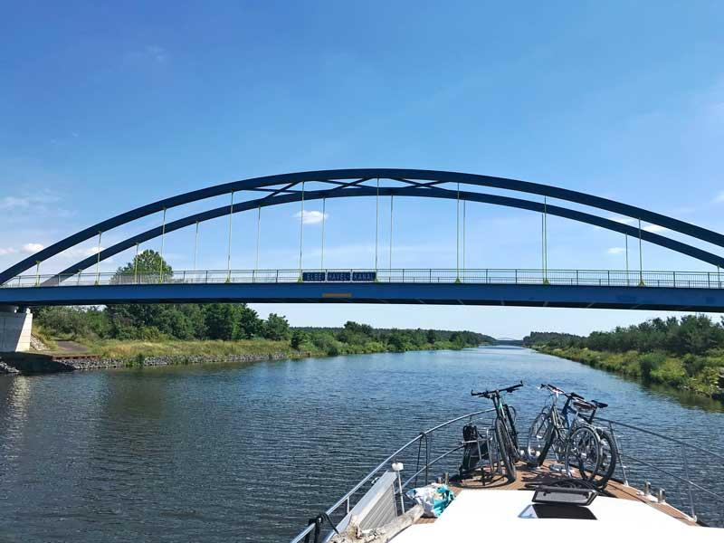 """Über den Elbe-Havel-Kanal spannt sich eine blaue Brücke mit dem Schild """"Elbe-Havel-Kanal"""""""