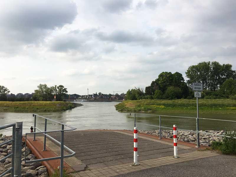 Im Vordergrund der Fähranleger und die Flutmulde, dahinter der Rhein und auf der anderen Flussseite die Stadt Rees