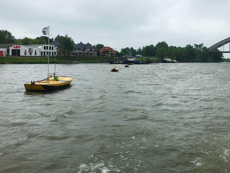 Gelbe Bojen in Form kleiner Bötchen markieren die Führungsleine der Fähren auf dem Niederrhein