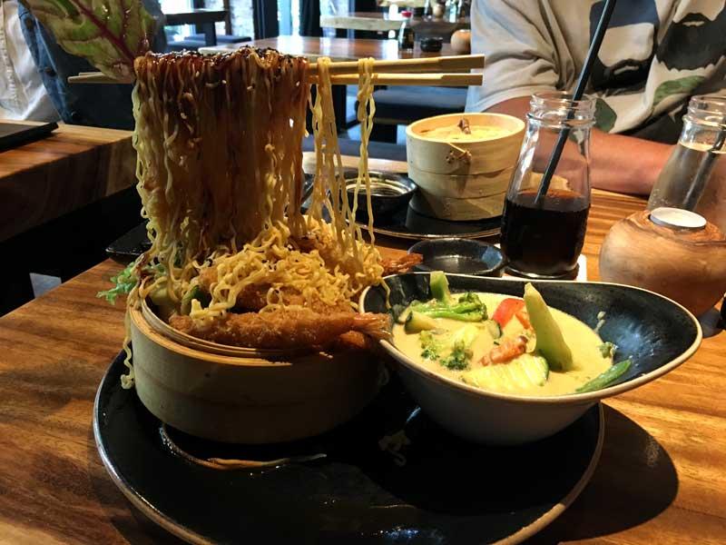 Das asiatische Nudelgericht ist so angerichtet, dass es aussieht, als würde ein paar Stäbchen mit Nudeln darauf in der Luft schweben