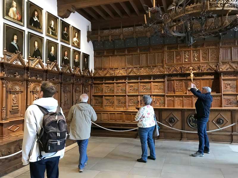 Der Friedenssaal im alten Rathaus von Münster ist gut besucht. An den Wänden hängen Portraits der Vertreter der Verhandlungsdelegationen