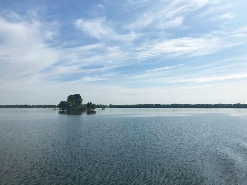"""Der See de Bijland ist ruhig und idyllisch. Vor der kleinen Insel dümpelt ein Minihausboot """"Happy Floß"""""""