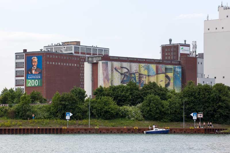 Eine große Industrieanlage am Rande von Münster ist großflächig und recht schön bemalt, dazu ein Bild von Raiffeisen