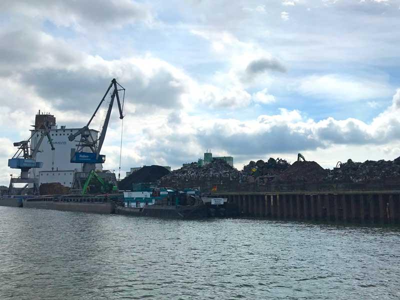 Ein Frachtschiff liegt im Hafen Braunschweig am Quai und wird mit großen Kränen mit Metallschrott beladen