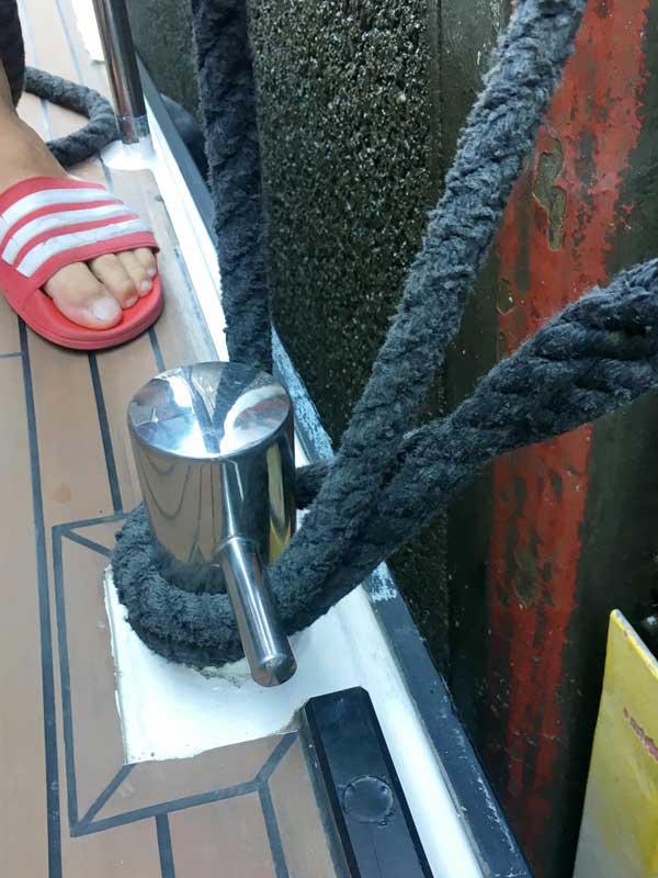 An der Klampe in der Mitte des Boots ist die Leine mit einem Auge befestigt. Die Leine wird um den Poller der Schleuse herumgeführt und dann noch einmal mit einer Schlaufe über den Poller gelegt.