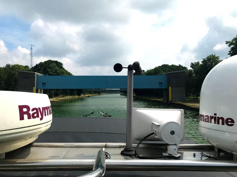 Blick über unseren Geräteträger zwischen Radar und Satellitendom hindurch auf das niedrige Sicherheitstor der Flutschleuse auf dem Mittellandkanal