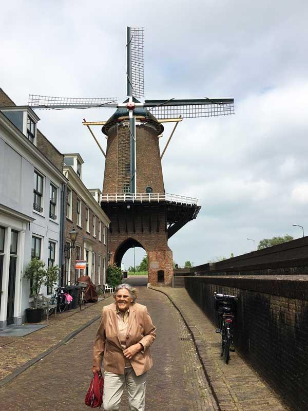 Eine ältere Dame läuft lachend vor der Windmühle von Wijk bij Duurstede über die Straße