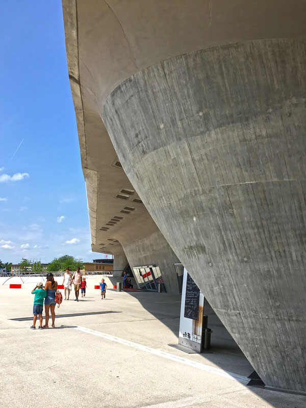 In der wunderschönen geschwungenen Flucht der Betonfassade des phæno Wolfsburg ist ein Aufsteller für ein Café so ungeschickt plaziert, dass er den Blick völlig zerstört