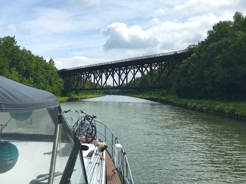 An einer Stelle hinter Braunschweig  wird der Mittellandkanal von einer riesigen rostigen Brücke überspannt, die äußerst baufällig aussieht