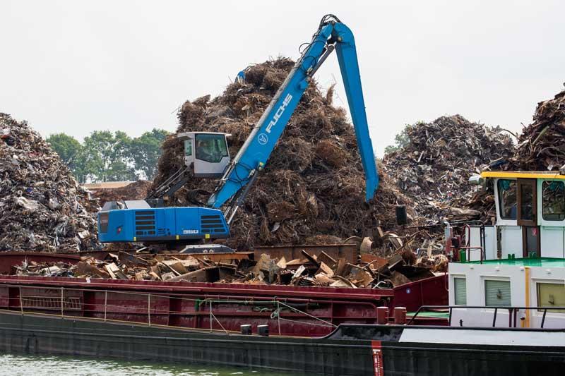 Sortier- und Verladestation für Metallschrott am Mittellandkanal; ein Bagger belädt ein Frachtschiff
