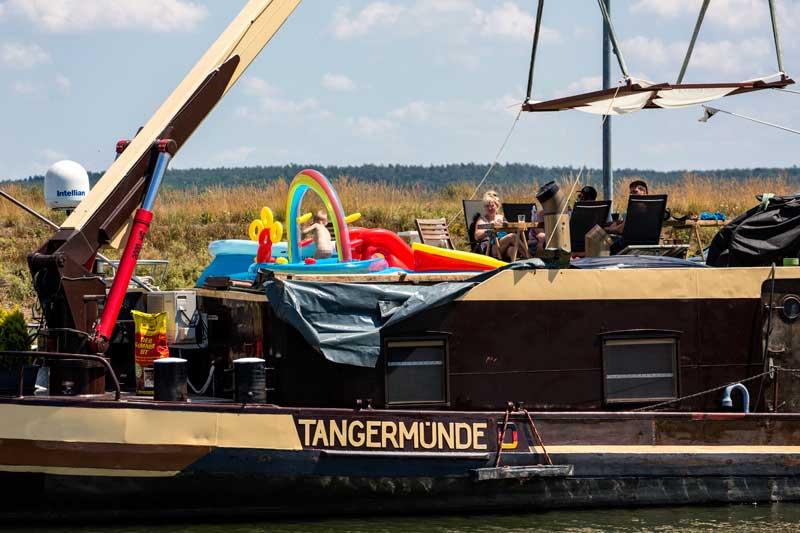 Auf einem Frachtschiff auf dem Mittellandkanal macht sich die Familie einen gemütlichen Sonntag mit Planschbecken für das Kleinkind und Sonnensegel am Autokran