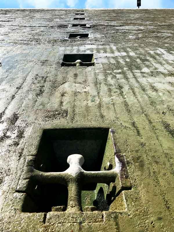 Wenn man die Wand der Schleusenkammer von ganz unten hochschaut, sieht man die regelmäßig übereinander angeordneten Stahlpoller in Nischen