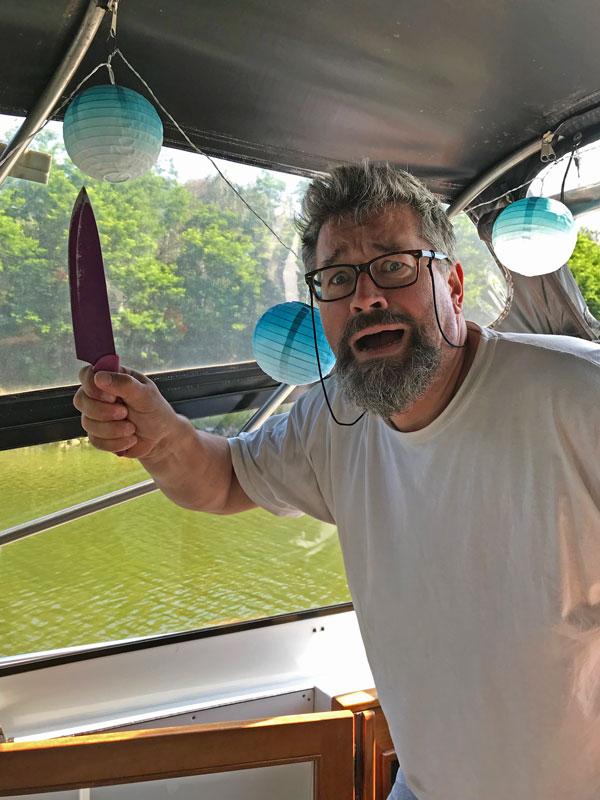 Thomas kommt mit dem panischem Gesichtsausdruck und erhobenem Messer aus der Kajüte gerannt