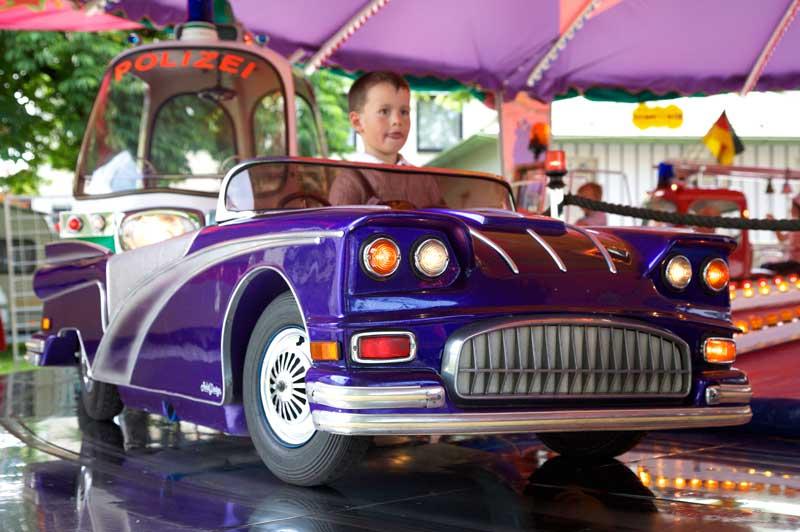 Kind in einem Auto auf einem Kinderkarusell