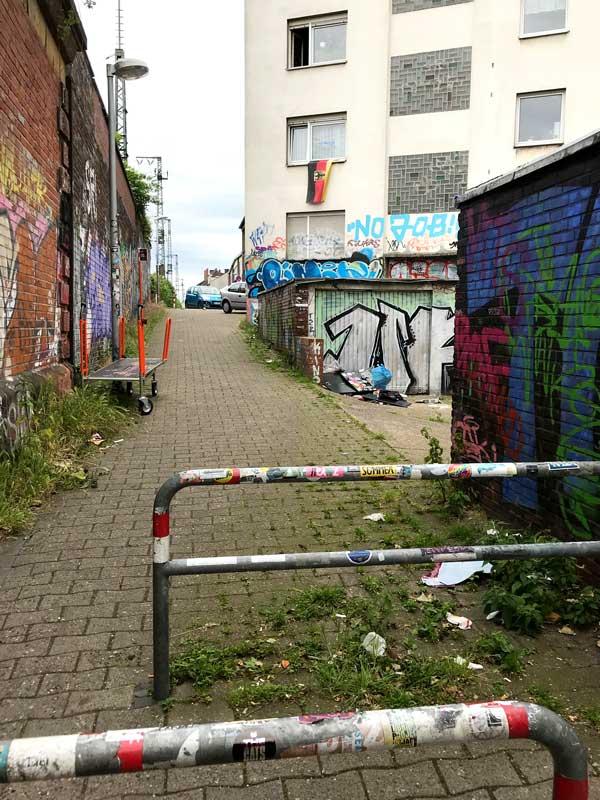 Ein mit Graffiti beschmierter Durchgang unweit des Stadthafens Münster. Aus einem Fenster hängt eine Bundesflagge