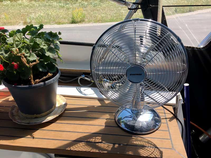 Da es sich unter der Persenning in der Sonne stark aufheizt, bin ich froh um meinen Ventilator, der neben mir steht und für Durchzug sorgt