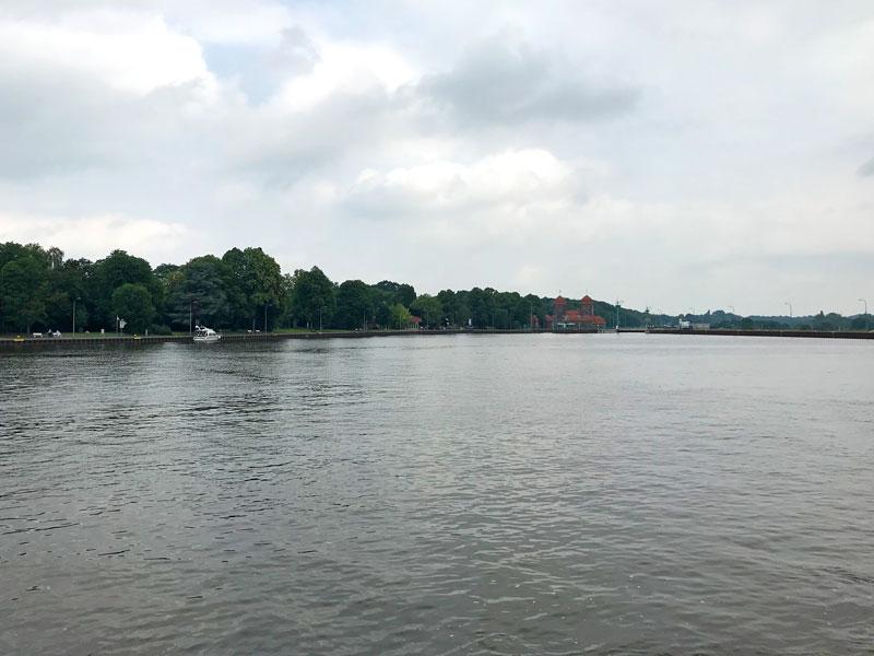 Blick vom Mittellandkanal zur Schleuse, die den Abstieg zur Weser ermöglicht. Es ist ein imposanter alter Ziegelbau mit mächtigen Türmen.