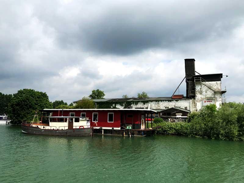 Weiter hinten im Kanal liegt links der Dorstener Motor Yacht Club e.V. an einem verfallenen alten Industriegebäude, an das ein Hausboot angedockt hat