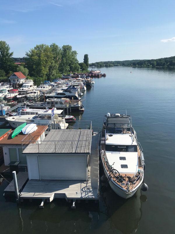 In der Marina am Tiefen See in Potsdam haben wir mit unserer Yacht außen an dem Schwimmfloss mit dem Gästezimmer der Marina angedockt. Blick über den Tiefen See Richtung Glienicker Brücker - links das Kulturquartier Schiffsbauergasse, gegenüber das Ufer von Babelsberg
