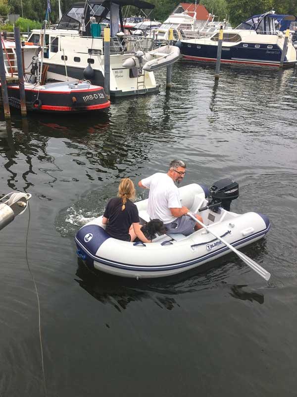 Thomas rudert im Hafenbecken der Marina am Tiefen See in Potsdam wieder zu unserer Yacht zurück. Mit an Bord sind der gerettete Hund und seine Betreuerin
