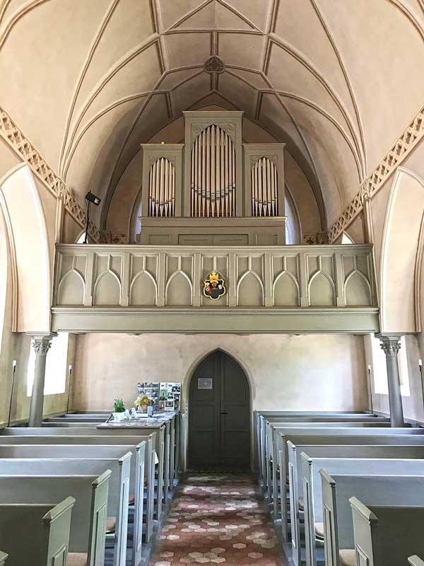 Das Innere der Dorfkirche von Paretz bei Ketzin Havel ist hell und in freundlichen Grün- und Blautönen gehalten. Hier Blick auf die Orgel über dem Eingang sowie Sitzbänke