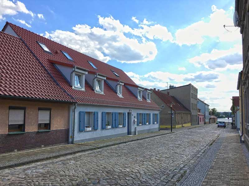 Straße in Ketzin Havel, die mit altem, holprigem Kopfsteinpflaster belegt ist. Zu beiden Seiten stehen niedrige alte, schön renovierte Wohngebäude