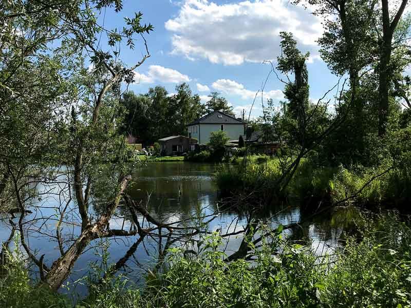 Blick übers Wasser auf ein Haus der Kliemsiedlung in Ketzin Havel, wild und verwunschen