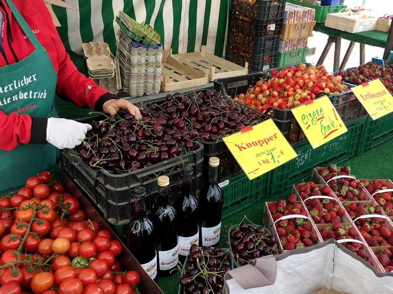 Marktstand in Werder Havel mit Werder Knupper (Kirschen in zwei Farben, einmal klassisch kirschrot und einmal hellrot-gelb) sowie Erdbeeren und Tomaten