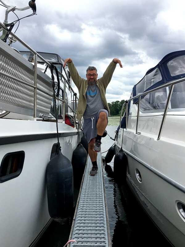 Thomas steht auf einem Bein zwischen zwei Booten auf dem superschmalen Steg des Yachthafens Scheunhornweg in Werder