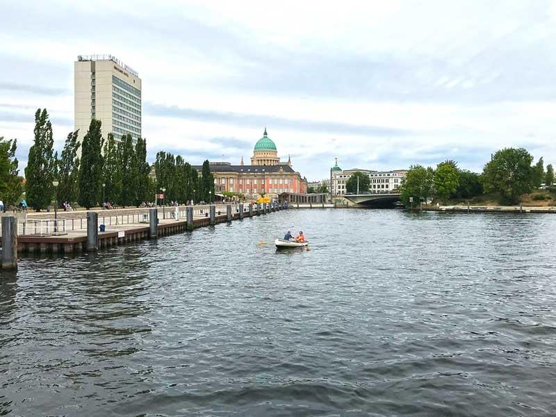 Ein Ruderboot mit zwei Menschen auf der Havel im Potsdamer Hafen. Im Hintergrund die Stadtansicht mit historischen Gebäuden und dem Mercure Hotel