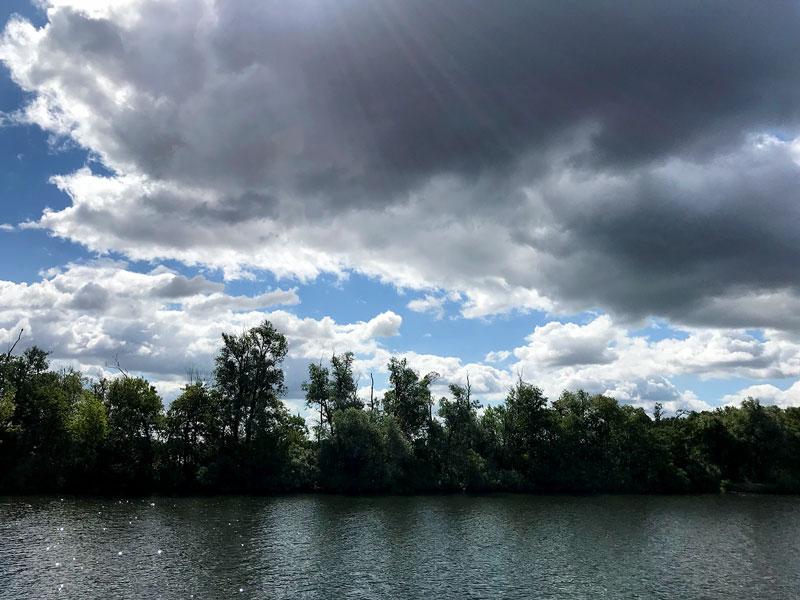 Die Sonnenstrahlen bahnen sich einen Weg durch dunkle Wolken über der Potsdamer Havel zwischen Ketzin und Werder