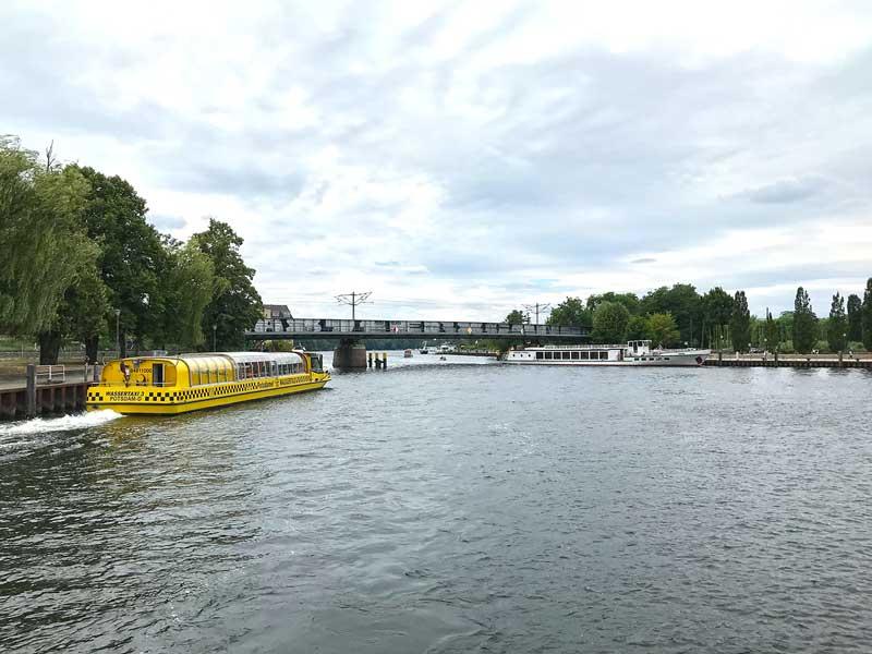 Ein großes gelbes Wassertaxi und ein Ausflugsboot kreuzen auf der Havel vor einer Brücke in Potsdam