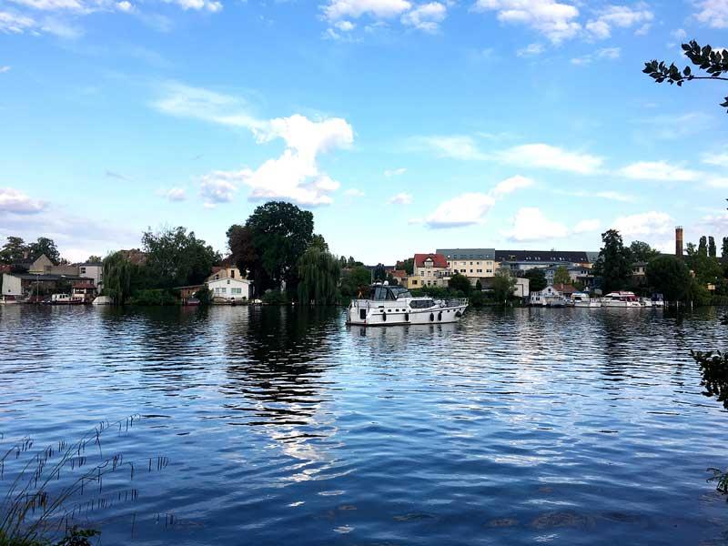 Das Boot liegt vor Anker auf dem Wasser der Bucht bei der Schlossinsel Köpenick bei Berlin