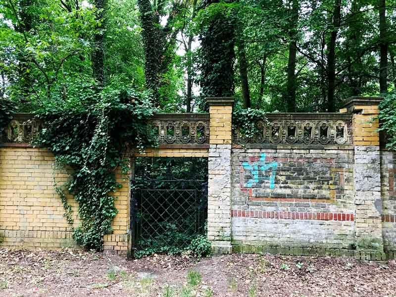 Gusseisernes Tor und alte Mauer von Pflanzen überwuchert am Glienicker Park an der Glienicker Lake bei Potsdam